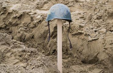 Elmetto di un soldato in una trincea sulla spiaggia