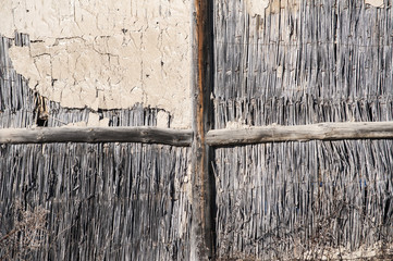 Wall of rural ramshackle barn of reed and clay as background