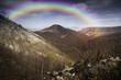 rainbow over mountain on summer day