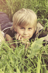 Portrait of child boy on green grass outdoors