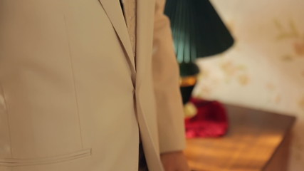 The man wears a jacket, fastened button, corrects cuff
