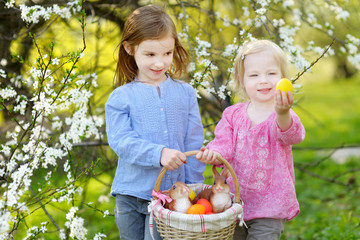 Two little girls holding a basket of Easter eggs