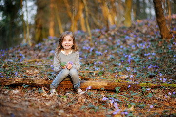 Adorable girl picking the first flowers of spring