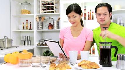 Young Ethnic Couple Wireless Tablet Enjoying Breakfast Home Kitchen
