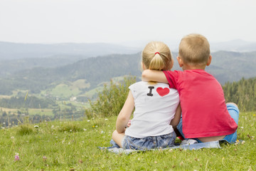 girl and boy sitting on a mountain