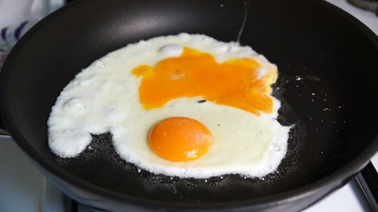Two fried egg yolks fried in a stone pan on a gas stove