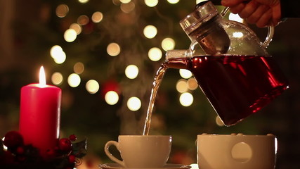 Pouring tea to teacup against Christmas background
