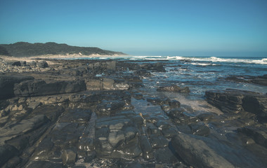 Dark rocks with blue sky at the wild coast of Morgans Bay. Easte