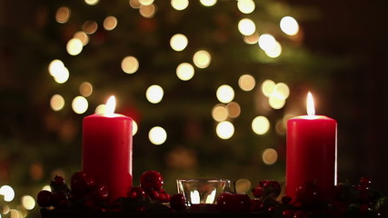 Two red candles with christmas atmospheric light in background