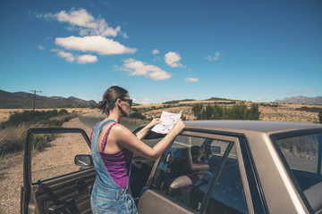 Woman standing next to old car reading a map. Swartberg. Western