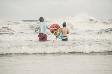 Father and son walking with bodyboard into the waves of ocean.