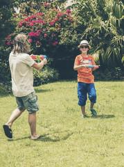 Young man and teenage boy playing with water gun in garden.