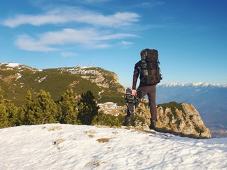 Tourist with big backpack and snowshoes standing on rocky view.