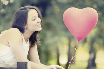Smiling Young Woman with a Red Shaped Heart