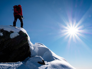 Mountaineer standing at the top of the mountain.