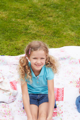 Girl Relaxing On Blanket During Camping Holiday