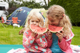 Children Enjoying Picnic Whilst On Family Camping Holiday