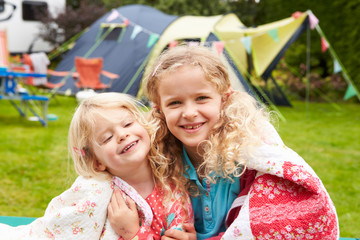 Two Girls Relaxing On Blanket During Family Camping Holiday