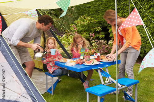 Tuinposter Kamperen Family Enjoying Meal Outside Tent On Camping Holiday