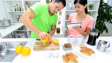 Young Ethnic Couple Wireless Tablet Preparing Breakfast