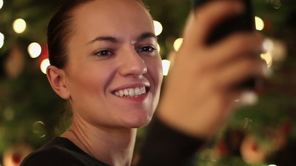 Young pretty woman taking selfie near Christmas tree