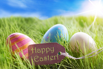 Easter Eggs On Sunny Green Grass With Label Happy Easter