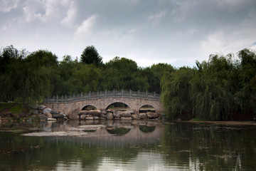 Traditional Chinese stone bridge across the lake lost in green t