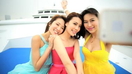 Successful Asian Chinese Female Friends Sailing Yacht Smart Phone Technology
