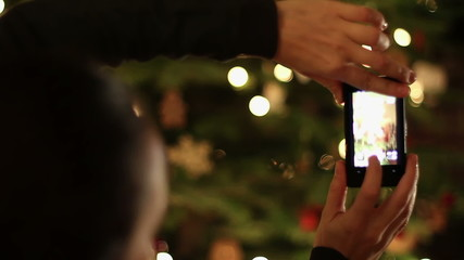 Young woman taking picture of christmas tree, close up