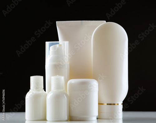 Leinwandbild Motiv Group of cosmetic bottles on dark background