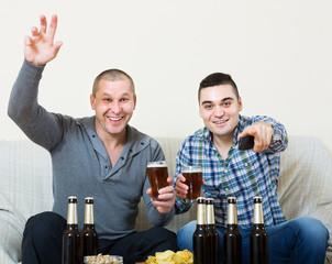 Two men watching football with beer indoor
