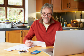 Mature Man Looking At Home Finances In Kitchen