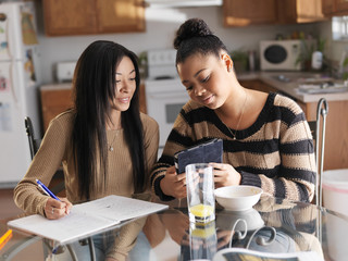two girls doing homework and using tablet