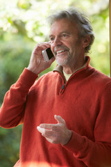 Mature Man Using Mobile Phone At Home