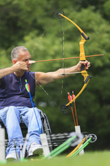 Man with spinal cord injury aiming a bow and arrow