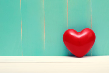 Red shiny heart on vintage teal wood