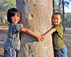 Asian little girls hugging a tree