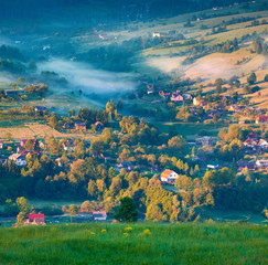 Foggy summer morning in the mountain village.