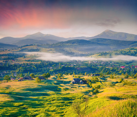 Сolorful summer sunrise in mountain village.