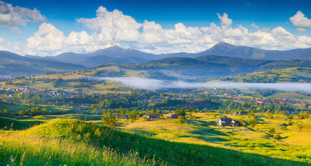 Panorama of the colorful summer morning in mountain village.