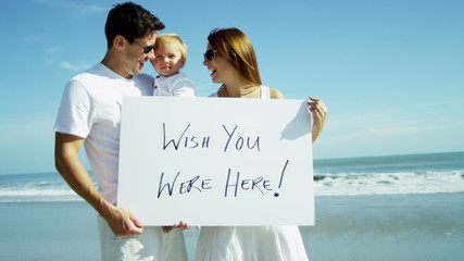 Happy Caucasian Couple Baby Holding Vacation Greeting White Board