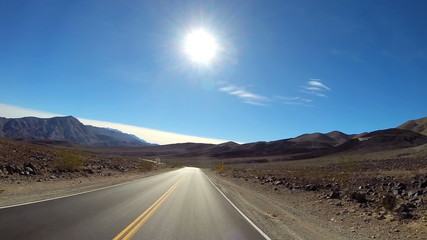 POV road trip Death Valley hot dry landscape vehicle motion sun flare USA
