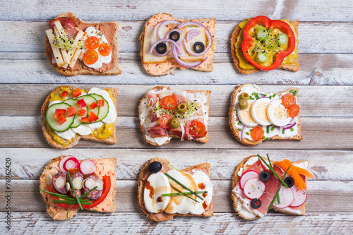Plexiglas Snack Sandwiches on wooden background, top view