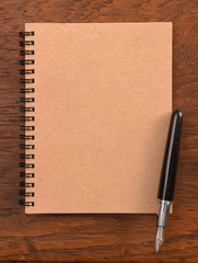 Notebook and pen on wooden background