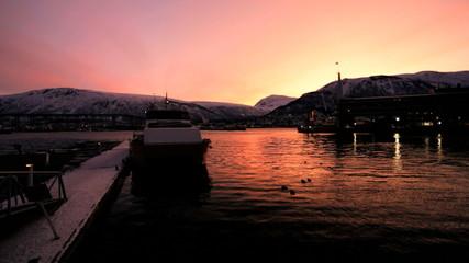 Norwegian skyline Tromso Harbour fading light red glow setting sun Fjord