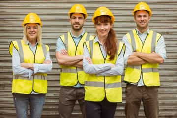 Warehouse team with arms crossed wearing hard hat