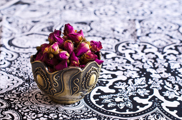 Dried rose buds in a metal Cup