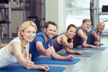 sportler im fitness-studio zeigen daumen hoch