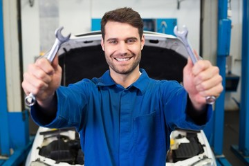 Mechanic holding pair of wrenches