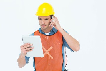 Carpenter using digital tablet and mobile phone